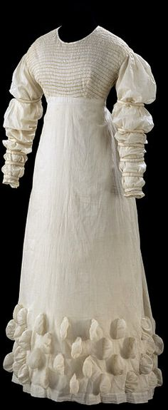 The combination of white muslin and puffed decoration on this dress reflects a mixture of historical influences. As with most garments of this period, we cannot pinpoint exactly where each detail comes from. They are often fanciful interpretations of past styles. The general shape, with its raised waistline and long, white, soft clinging fabric, is loosely