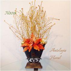 Arreglo en base de latón con helechos y noche buena artificiales en tonos dorado y naranja...