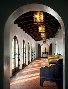 Long hallway with rounded, Spanish arches and beams on the ceiling. Love the floors! MM Interior Design