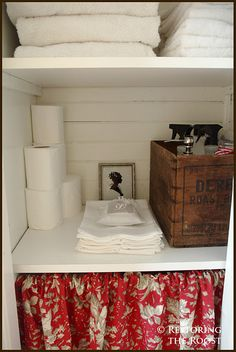 Organized linen closet with skirted shelf and rustic crate storage!  I really like the idea of the tension rod and curtain. Seems very homey.