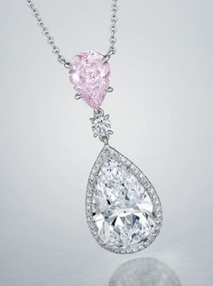 A COLORED DIAMOND AND DIAMOND PENDANT NECKLACE. Suspending a 5.06 carat pear-shaped diamond, trimmed with circular-cut diamonds, and a 1.68 carat modified pear-shaped fancy purplish pink diamond, to the fine link neckchain, mounted in platinum.