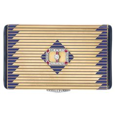 Art Deco Gold, Platinum, Enamel, Diamond and Ruby Case, Cartier  14 kt., the rectangular case applied with slender blue enamel lines, the sides decorated with a geometric pattern of blue enamel bands, with black enamel sides, surmounted by a platinum, diamond and ruby buckle ornament, with diamond-set thumbpiece, signed Cartier, circa 1930, buckle circa 1920, added later, approximately 81 dwt. 1 3/4 x 3 inches.