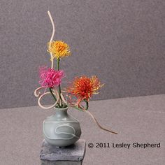 Arrangement of dollhouse scale spider chrysanthemums in a miniature celadon vase.
