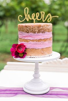 """Brides: One-Tier Naked Wedding Cake with Pink Frosting and a Laser-Cut Topper. A one-tier naked wedding cake filled with pink frosting and decorated with a laser-cut gold """"Cheers"""" topper, created by Ashley Bake Me a Cake."""