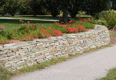 Retaining wall constructed of Colonial Wall Stone creates a beautiful planting bed area.