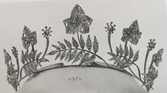 a diamond tiara with five ivy leaves, five leaf fronds and four unidentified flower-heads, all rising on their own pinnacles from a simple base