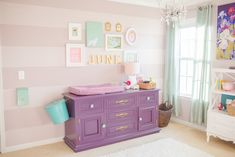 Love this vintage dresser repainted and being used as a changing table in this purple nursery!