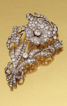 DIAMOND BROOCH, CIRCA 1890.  Designed as a tied foliate and floral spray decorated with a central en tremblant flower head, set throughout with cushion-shaped, rose- and circular-cut diamonds.