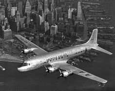 American Dc-6 Flying Over Nyc - New York, New York 1947 - The American Airlines DC-6 flagship Oklahoma flying over NYC. - by Underwood Archives