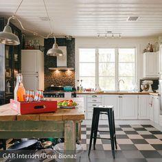 Zeitlos trifft auf Retro: Die eleganten Fliesen in Schachbrett-Optik und die Küchenschränke im zeitlosen Landhaus-Stil wurden hier mit einem Esstisch im…