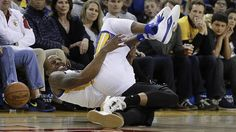 Golden State Warriors Andre Iguodala falls onto Portland Trail Blazers Damian Lillard during the second half of an NBA basketball game Friday, March 11, 2016, in Oakland, Calif.