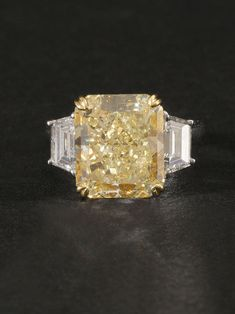 Norman Silverman Platinum Fancy Yellow Radiant Cut Engagement Ring with Trapezoid Side Diamonds. Center Diamond 7.53ct Fancy Yellow VS1 Quality. Side diamonds approximately 1.36ct total weight. Available at London Jewelers.