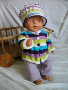 """Pletené oblečky pro panenku - barvy a pruhy Komplet tvoří pletený svetřík na tři knoflíčky, háčkovaná bekovka a fialové kalhoty v pase do gumy. Barvičky jsou pěkně """"koukavé"""", určitě potěší malou maminku. Vhodné pro panenku Baby Born (cca 42 cm)."""