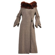 Lovely late 1920s/very early 30s fin sleeved wool coat with standing fox collar.  Dark mahogany fox collar crosses over stand high around the collar bones. Long skinny sleeves with tiered fins below the elbow. Classic asymmetric button closure. Amazing top stitched pleated details in back. Fully lined. Labeled Grocott & Co, Shrewsbury, England.