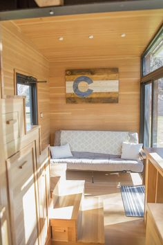 Inside the tiny house is a queen size bedroom loft and a futon that sleeps two. The kitchen has a half fridge, single-burner induction cooktop, and pantry.
