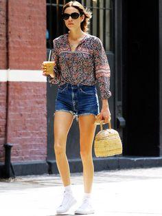 Alexa Chung beim Stadtbummel mit Jeansshorts und Boho-Bluse.