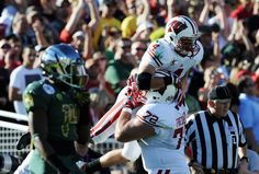 Travis Frederick Photos Photos - Wide receiver Jared Abbrederis #4 of the Wisconsin Badgers celebrates with Travis Frederick #72 after Abbrederis  scores on a 38-yard touchdown catch in the first quarter against the Oregon Ducks at the 98th Rose Bowl Game on January 2, 2012 in Pasadena, California. - Rose Bowl Game presented by Vizio - Wisconsin v Oregon