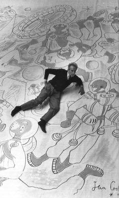 """Jean Cocteau en chaussettes avec ses astronautes, sur l'immense œuvre qu'il a conçue pour l'expo """"Terre et Cosmos"""", présente au Palais de la Découverte en 1958."""