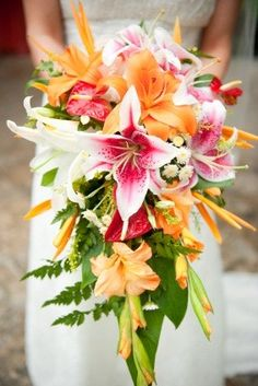 The bridal bouquet will be a cascading bouquet of orange asiatic liles, orange tulips, orange mokara orchids, green plumosa,  and dark purple lisianthus with green bud tips wrapped in burnt orange ribbon.  The shape of he bridal will be similar to this.