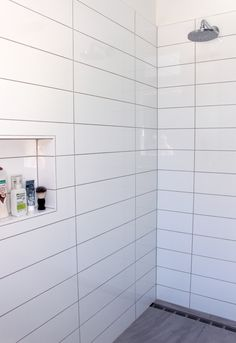 Grey concrete tile in the walk in shower, white tile grey grout