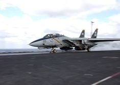"""A VF-103 """"Jolly Rogers"""" F-14D Tomcat launching from USS John F. Kennedy"""