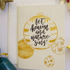 """A hand-painted Christmas card featuring the song lyrics from the Christmas carolJoy to the world:""""Let heaven and nature sing"""" lettered in black ink, surrounded by gold and silver Christmas baubles."""