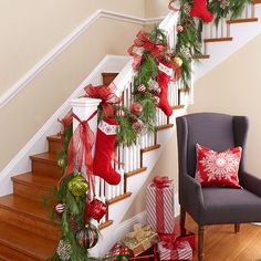 Showcase your family's Christmas stockings in a prominent location like this staircase. Add a garland and make it a focal point. Take it a step further with oversize Christmas ornaments. Finish the scene with a shimmery red snowflake pillow in a cozy chair and artfully wrapped packages on the floor.