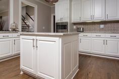Bright white raised panel island with granite countertops and a subway backsplash