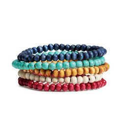 Multicolored. Elastic bracelets in various designs. Four bracelets made from wooden beads and one from reconstituted stone beads.