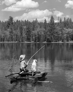 Boy huck finn style on homemade raft with dog fishing in lake, 1950,'s