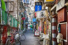 Shinjuku Golden Gai (新宿ゴールデン街) is a small area of Shinjuku, Tokyo, Japan, famous both as an area of architectural interest and for its nightlife. It is composed of a network of six narrow alleys, connected by even narrower passageways which are just about wide enough for a single person to pass through. Over 200 tiny shanty-style bars, clubs and eateries are squeezed into this area.