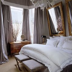 luxe, layered, and sophisticated.  gray walls, a set of gilded mirrors, and an antique dresser.
