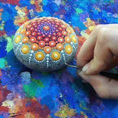"""Elspeth McLean is an Australian award-winning artist whose passion for colour and detail has evolved into a unique style of painting she describes as """"Dotillism"""". In what she calls Mandala Stones, McLean collects beautiful beach stones and uses them as her canvas to create intensely colourful and intricate artworks entirely out of dots."""