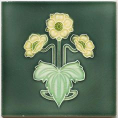 An Art Nouveau relief pressed polychrome tile featuring a triple flower head, stem, and leaf design in pale yellow and...
