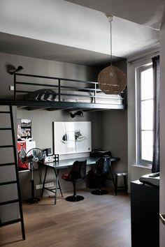 Antresola pozwoliła wygenerować w przestrzeni tego pokoju miejsce do spania i pracy. Czarne krzesła, biurko i dodatki harmonizują kolorystycznie z jej konstrukcją. Zaznaczenie aneksu biurowo-sypialnianego szarą farbą poprawiło proporcje wnętrza.