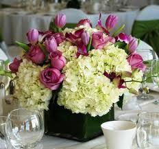 """The shorter centerpieces will be a combination of """"lemon-lime"""" hydrangeas, """"dreaming maid"""" tulips, """"princess Irene"""" tulips, mini purple calla lilies, mini mango calla lilies, and green lemon leaves in square vase."""