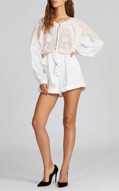 This long sleeve **Alice McCall** jumpsuit is rendered in cotton and features a jewel neckline with a deep keyhole in the front an a knife pleat at the back, broderie anglais embroidery detail at the bodice, and a self-tie high waisted short with a rolled hem.