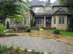 This home's driveway is a multi-material showcase. The homeowners desired overflow parking for entertaining, so Landscape Studio created a circular driveway with pavers. On the main driveway, decorative flagstone near the entryway accents the concrete.