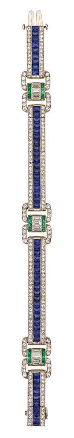 A diamond, sapphire and emerald bracelet, Oscar Heyman & Brothers designed as a central row of French-cut sapphires bordered by single-cut diamonds, accentuated by twin oval-shaped diamond panels joined by arches of baguette-cut diamonds and calibré-cut emeralds