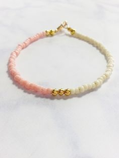 This wonderful friendship bracelet is made with pink, beige and gold beads. A beautiful and gentle color combination looks great and can be stacked with other beaded bracelets for a layering effect. B