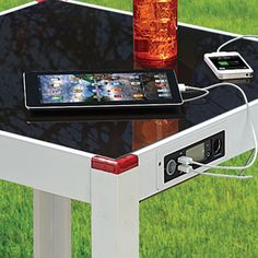 The Device Charging Patio Table - Hammacher Schlemmer, $299.95 Could try to make one myself.... would definitely motive it by adding a solar panel though (hooked up to a battery) ,  so it wouldn't have to depend on power from the AC.
