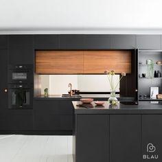 Blaun mattamustat ja tiikkipuiset ovet ja kaapistot sekä kupariset yksityiskohdat luovat keittiöön lämpimän ja ylellisen ilmeen. Keskellä olevat ruskeat ja kupariset pinnat pehmentävät mustaa väriä ja luovat keittiöön valoisuutta ja tunnelmaa.