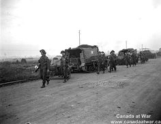 Canadian Infantry passing a tank gun as they move up. 25 july 1944, south of Vaucelles.