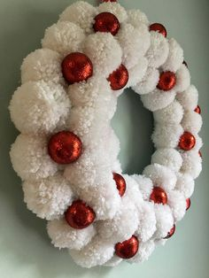 Get this wreath before it is gone!!!This Christmas Snowball Pom Pom Wreath is made from over forty handmade white yarn pom poms. The Pom poms are sprayed with a red glitter spray to add a touch of sparkle and is finished with red glitter ornaments. It is made on a 10 inch wreath