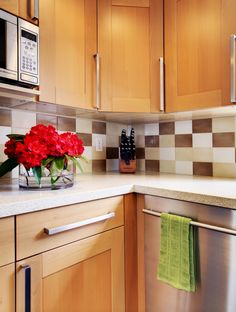 Neutral-colored backsplash tile from Ambiente goes all the way up to the bottom of the upper cabinets to make cleanup easy. The random color pattern in a straight-set arrangement makes the kitchen feel relaxed yet contemporary.