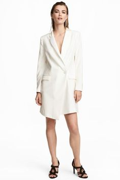 Short jacket dress in woven fabric with a wrapover and partly concealed double-breasted front. Flap front pockets, long sleeves with decorative buttons at t