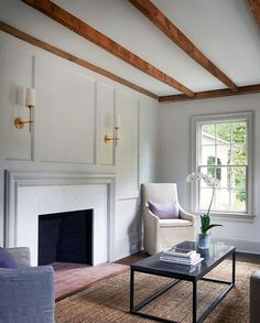 Chic living room boasts a rustic wood ceiling beams over a gray paneled fireplace wall lined with a gray fireplace mantle accented with a marble surround illuminated by antique brass sconces.
