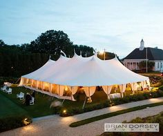 An amber glow drifts through sheer curtains of the wedding reception tent, lighting the white benches that surround.