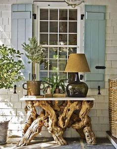 Inviting Outdoor Entrance Table ::: gnarled wood, woven basket and container plants bring textures, as well as soften the structure and stone patio.