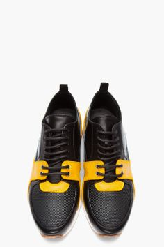KRISVANASSCHE // SSENSE Exclusive Black Leather & Suede Derby-Sneaker Hybrids 32134M050011 Low top leather shoes in black. Round toe. Derby style upper with black lace up closure and silver tone eyelets. Sneaker style toe with textured panel and rubber detail. Paneled upper in mustard yellow suede and blue leather. Pull loop at heel collar. Off-white rubber foxing. Tonal stitching. Available exclusively at SSENSE. Leather upper, rubber sole. Made in Italy. $1025 CAD
